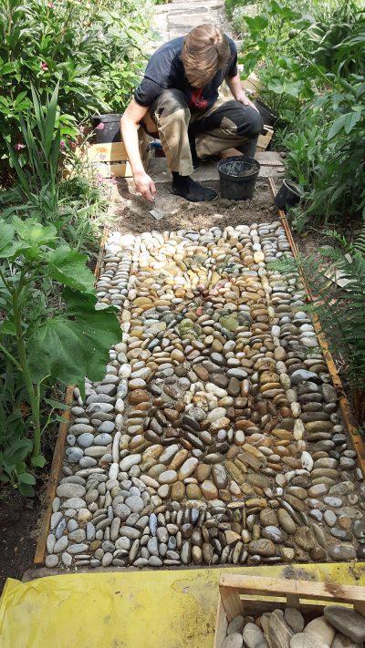Der erste Teppich als Gartenwegmosaik wird bearbeitet