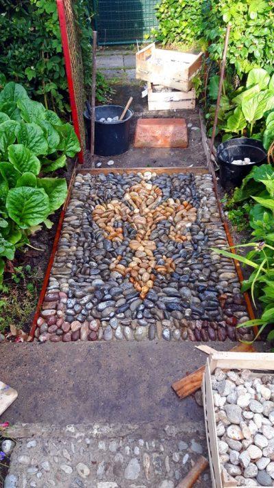 Die erste Lilie ist mit Kieselsteinen gelegt